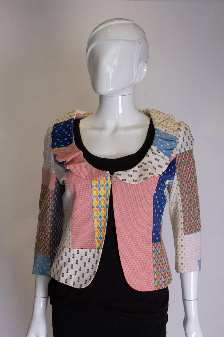A pretty patchwork jacket for Spring /Summer. The jacket has a frill around the collar , a one buttonn fastening and elbow length sleeves.