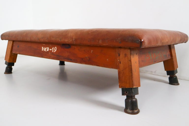 Strong, vintage European gymnasium bench with a patinated leather covered top that sits in to the bench's solid wooden frame. The gym bench frame maintains its original markings where the straps and rings were once held. Each of the four legs has a