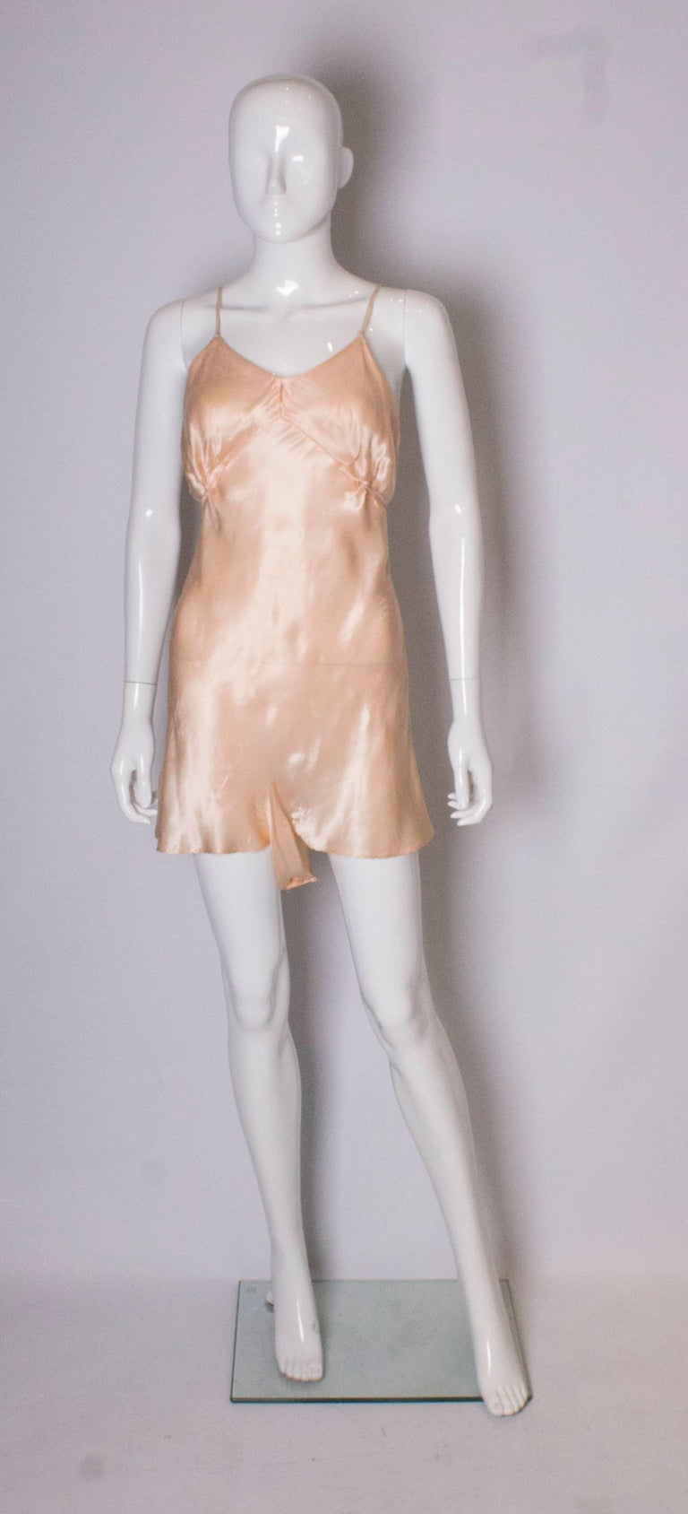 A pretty peach satin  cami nickers with tie detail on front and spagetti straps.