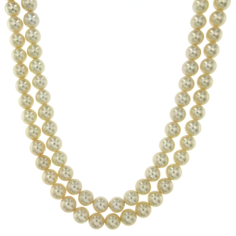 This beautifully crafted pearl necklace features great quality Japanese white pearls 8,5 mm. with a precious 18k white gold flower clasp, set with colorless diamonds (F color vvs) weight 1.20 carat and fine Sapphires in the center 2.50 ct. The pearl