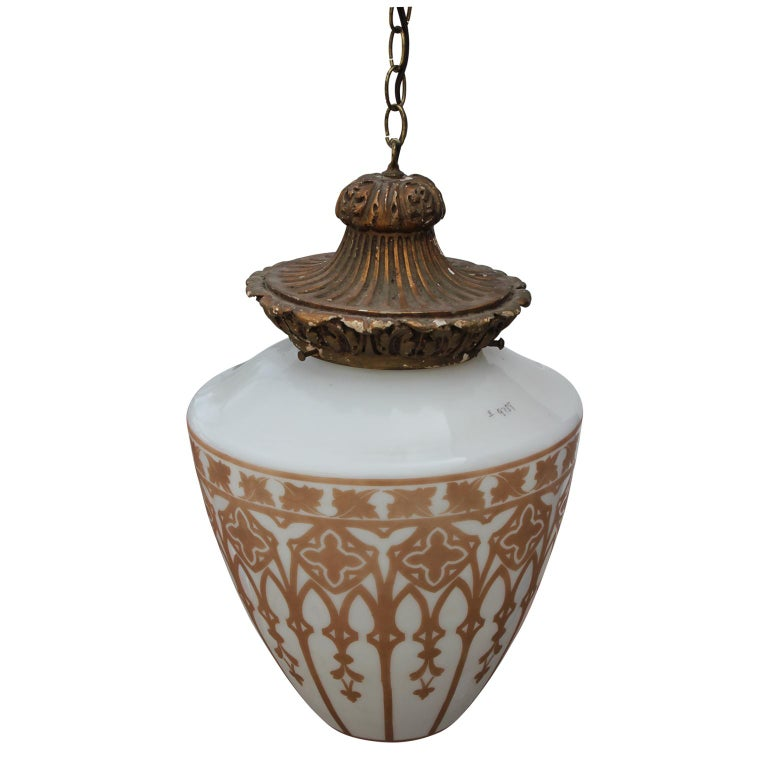 Stately vintage pendant light. It has a gold leafed base that holds the teardrop glass drum. Gold architectural stencils decorate the outside of the white glass, reminiscent of a stained glass window.