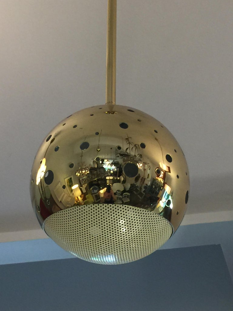 Polished brass perforated grill globe allows for light throughout fixture.