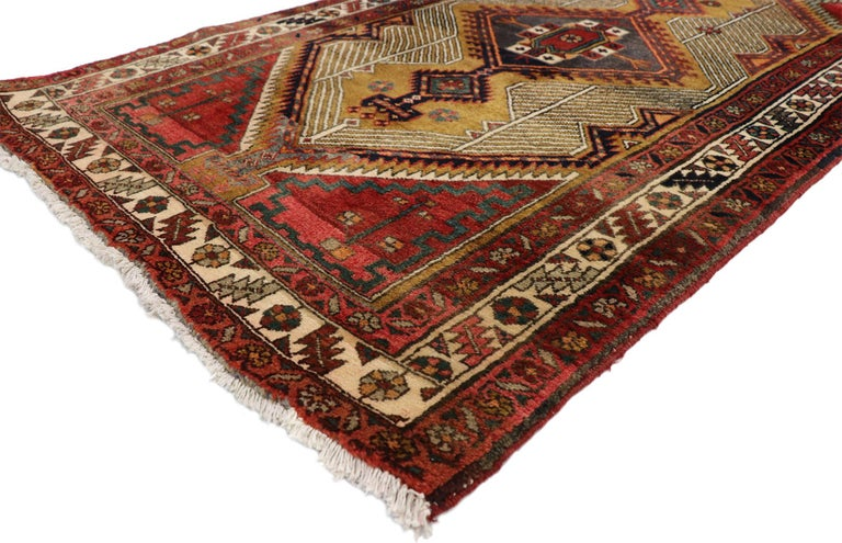 75338, vintage Persian Azerbaijan runner with Tribal Art Deco style. This hand knotted wool vintage Persian Azerbaijan runner features a column of three distinctive latch-hook medallions flanked with lozenges and amulets at either end. A background