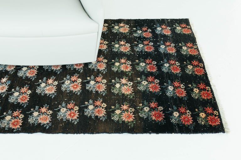 A charming and unique vintage Persian Bakhtiari with a beautifully designed all-over floral design. The black field is the perfect backdrop for the bright and lively pink and red florals. The traditional floral designs, a characteristic of the