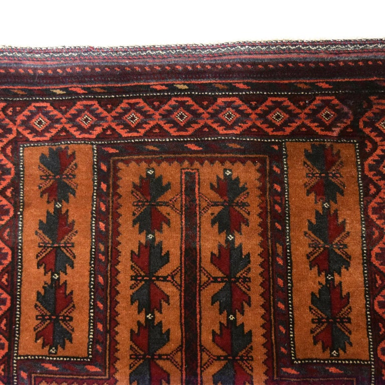 """In warm shades of red, gold, black, and cream wool, this Persian Balouchi belongs to Orley Shabahang's World Market collection. Measuring 2'10 x 4'6"""", this carpet is completely hand-knotted using a traditional Persian weaving technique. This weave"""