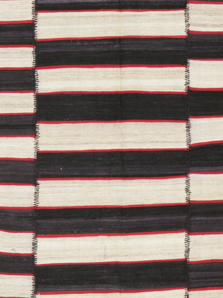 A vintage Persian flat-weave Kilim from the mid-20th century. Totally graphic and chic, this five-panel composite pileless carpet has black and ecru stripes alternating and slightly staggered overall with red narrow stripes joining the two. No