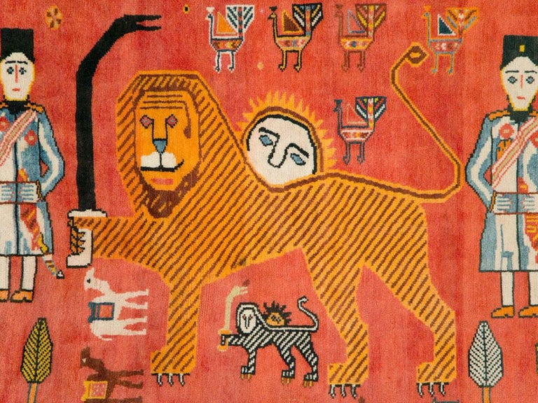 A vintage Persian Gabbeh rug from the late 20th century with a pictorial design of the Persian 'lion and sun' motif on a red-orange field. The design is quite fine and curvilinear for a tribal piece that is often quirky and geometric. The condition