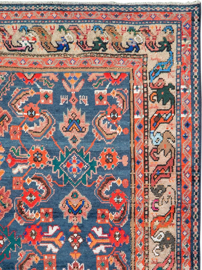 A vintage Persian Hamadan rug. The blue field abrashes (natural color striations) from dark to medium while displaying a classic Herati design accented with white cotton and showing small interstitial animals. The sand-putty border features the