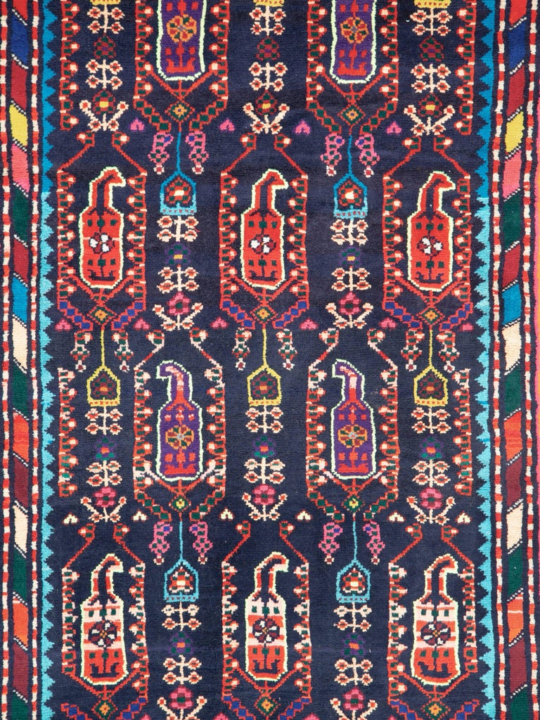 A vintage Persian Malayer folk rug in runner format from the mid-20th century. The primary field and border colors are midnight blue and orange with secondary devices that are bright and multicolored.