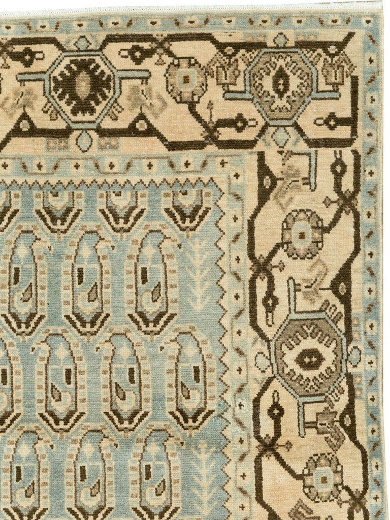 A vintage Persian Malayer rug from the mid-20th century. The beige border consists of dark brown vines attaching geometric palmettes. The blue-green field is stylized with botehs (paisley motifs).  Measures: 3' 8