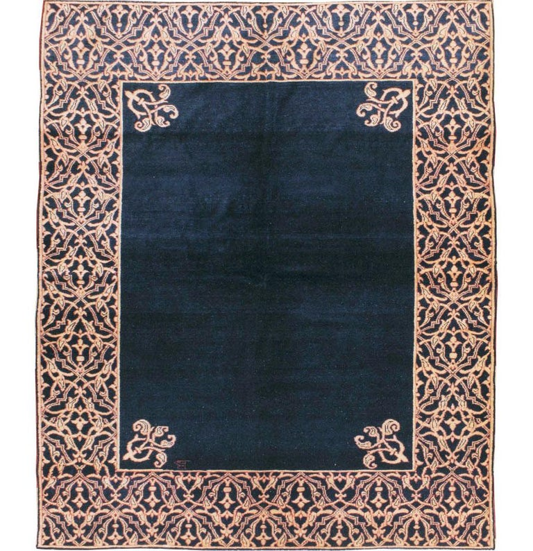 A vintage Persian Malayer area rug handmade during the mid-20th century with a solid navy blue colored field and an intricate Art Deco style arabesque border. The design is very versatile and works well with both European Renaissance traditional