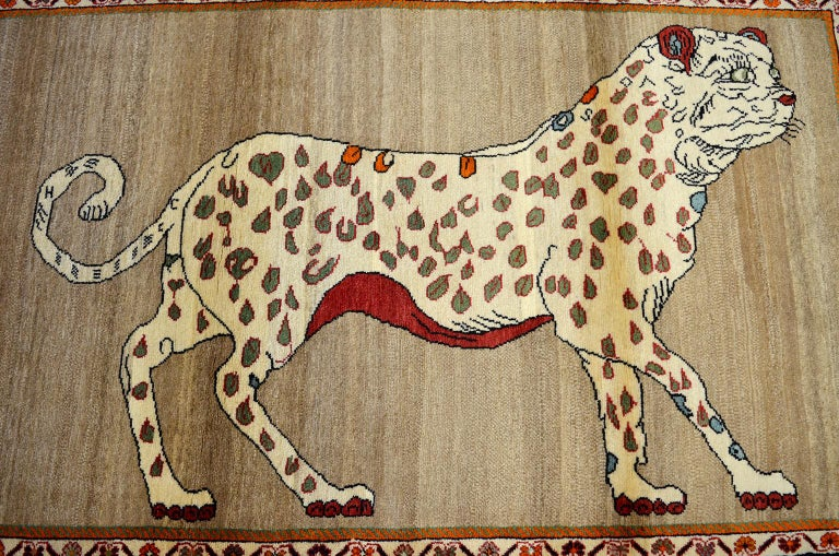 This vintage Persian Qashqai leopard animal carpet, circa 1930 in pure handspun wool and organic vegetable dyes has a unique coloration of undyed cream, beige and gray wools and contrasting dyed red, burgundy and light blue tones. The leopard's