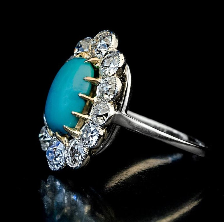 Circa 1920s  This Art Deco era platinum and gold (prongs) cluster ring features a Persian turquoise cabochon framed by bright white and very sparkly old European and old mine cut diamonds (F-G color, SI clarity).  The turquoise measures 10.52 x 7.54