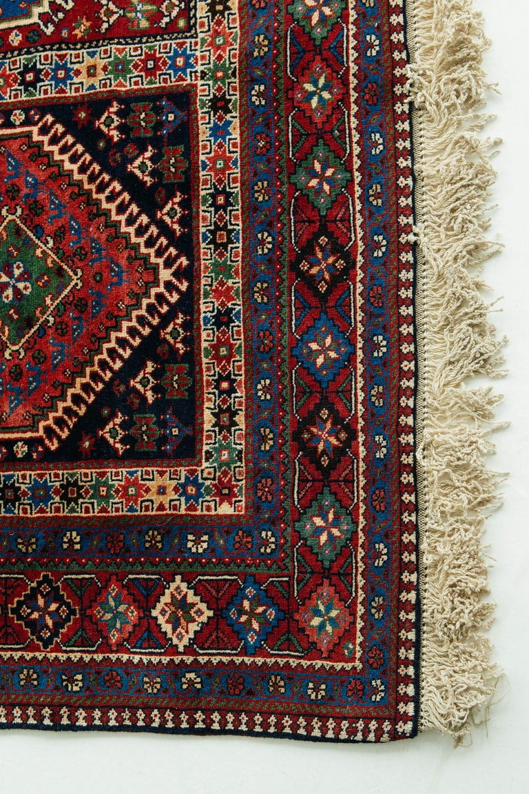 This antique Yalameh rug in deep red, blue, green, black, and ivory tones. The field pattern consists of rectangular compartments with latch-hook diamond medallions and varied fill motifs, including stars and talismans. The main border features