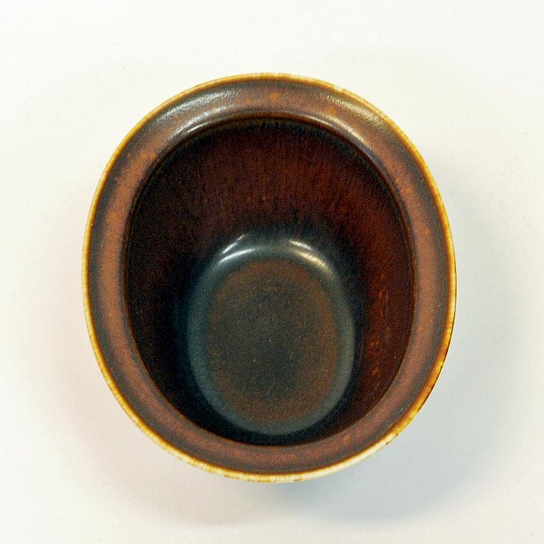 Practical midcentury stoneware bowl by Gunnar Nylund for Rörstrand, Sweden, 1950s. Perfects size for nuts, sugar, sauces, spices etc. or just for decoration. Lovely rustic brown color. Measures: H: 13.5cm L x 11 cm H x 6 cm D. Glazed bronze