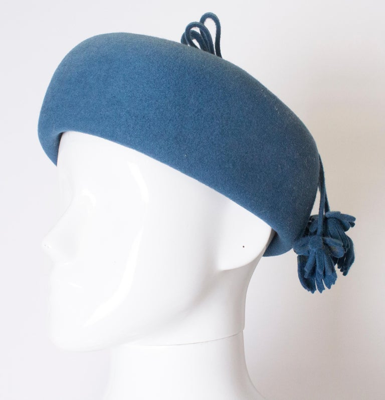 A chic hat for Fall , in a stunning petrol blue colour.  The hat is an oval pill box shape, and measures 3'' in height, and has a inner circumference of 22''.