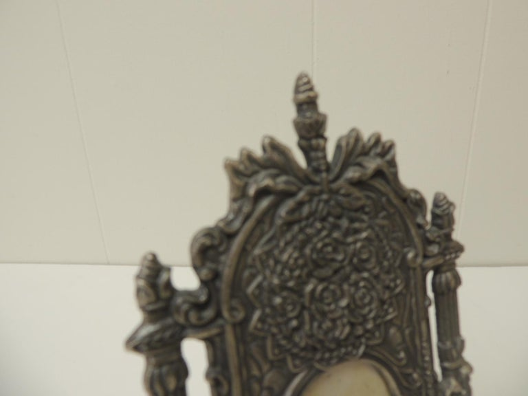 Vintage pewter picture frame in shape of a cheval floor mirror. Velvet backing. The frame depicts, flowers, tassels, columns and bows. Inside image ot picture size: 2 x 3 Size: 5 x 8 3/4 x 1/4 inch thick.