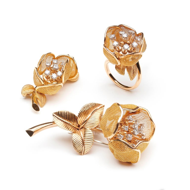 A vintage Piaget diamond and gold flower suite, comprising a ring, designed with articulated gold mesh opening and closing petals, diamonds set stamens and textured finished leaves, together with two diamond set flower brooches, both with gold mesh