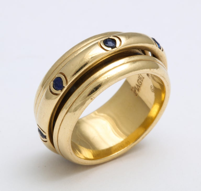 What a wonderful and different ring here shown in 18 Kt gold and sapphire. The center band rotates giving the band a nickname of a fidget ring. The bordering bands are ridged in contrast to the sapphire band being smooth. Texture adds to the appeal.