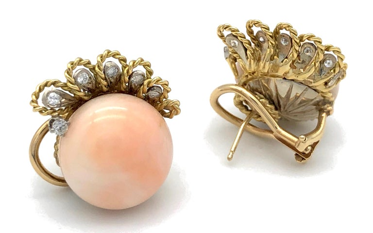 This pair of earclips features wonderful pink coral boutons mounted on 18k gold.  Each clip is decorated with six platinum mounted diamonds, five diamonds are surrounded by loops made of twisted gold wire. At the moment one of the clips has a stud
