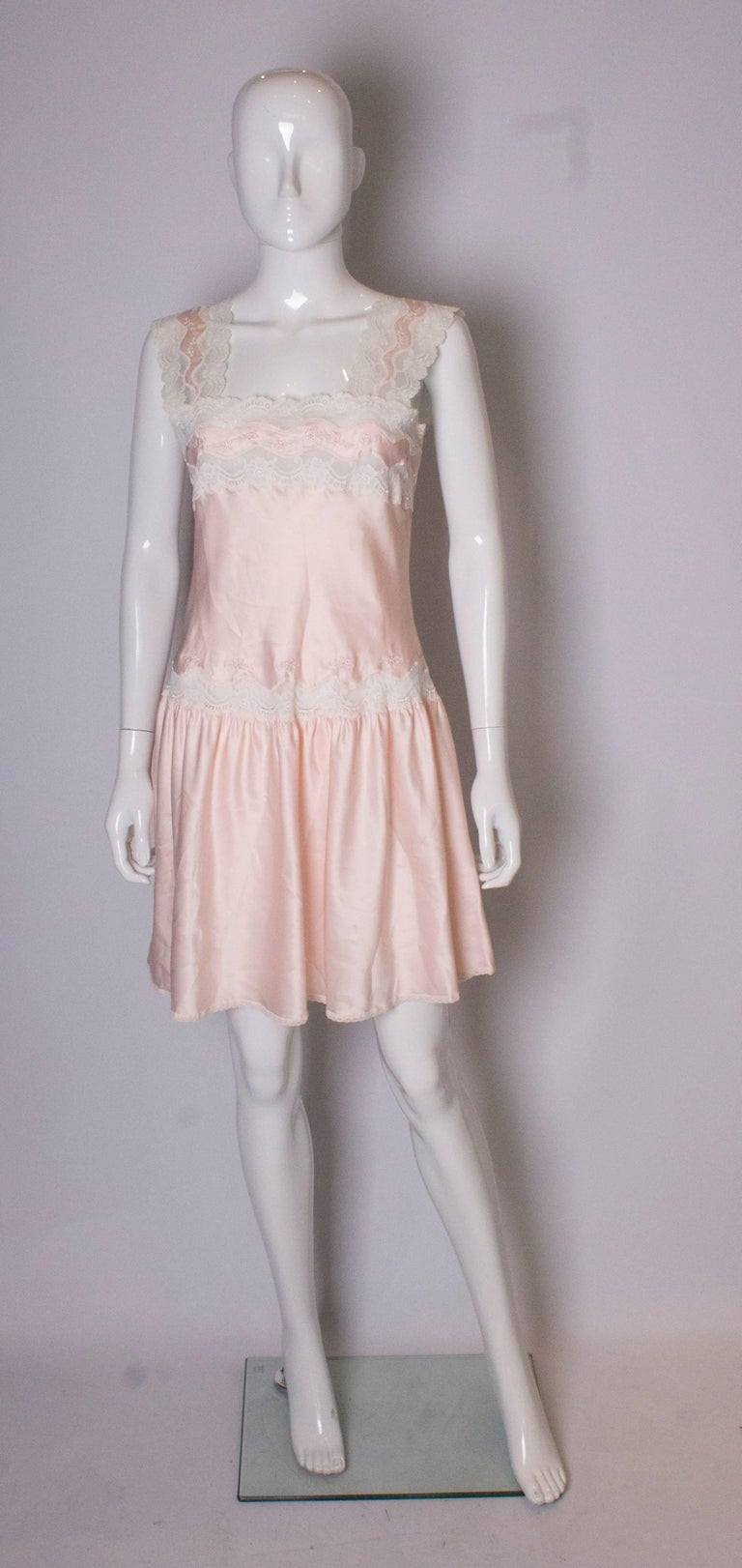 A charming vintage dress ( or nightdress ) by Marks and Spencer. In a pale pink with lace and embroidery trim, the dress has a drop waist and wide shoulders.