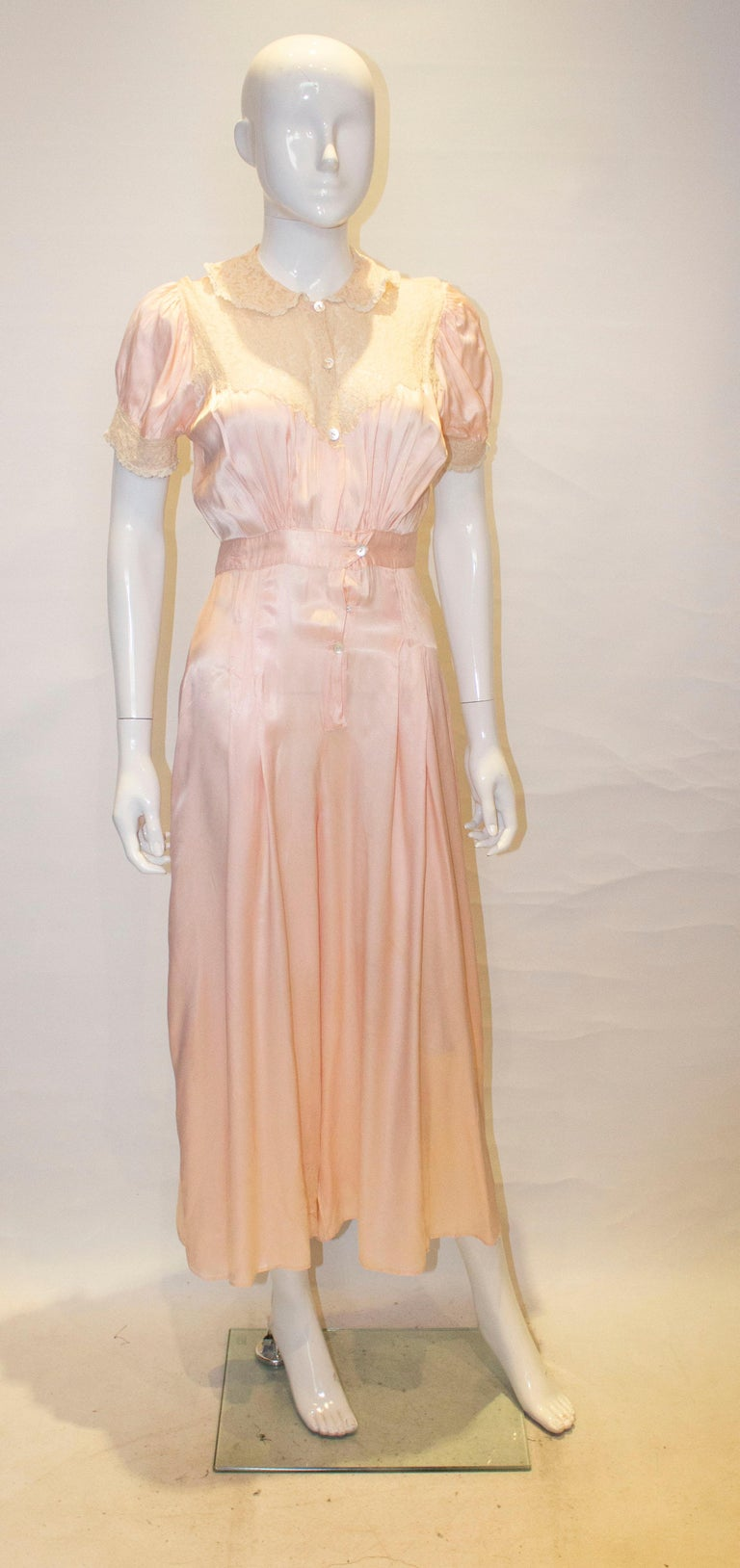 A stylish and unusual jumpsuit.  In a pretty pink satin, it has a lace collar and trim on the bodice and cuffs. It has a five button front opening with gathering at waist leval front and back, and pleats and hip leval front and back.  Measurements: