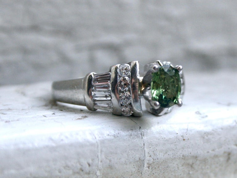 I just can't resist the classic beauty of this Beautiful Vintage Green Sapphire and Diamond Engagement Ring. Crafted in Platinum, the design features a stunning Green Sapphire Center, surrounded by Round Brilliant and Baguette Cut Diamonds. In the