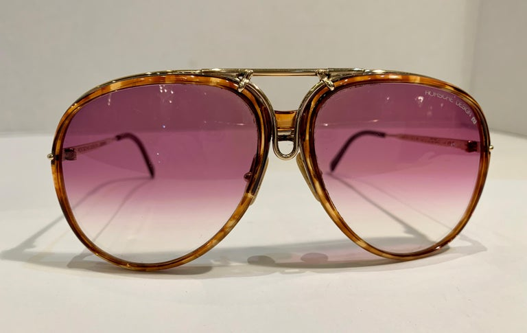 Vintage, ultra-rare 1980's innovative Porsche Design by Carrera large gold metal aviator style sunglasses.   Frame features two sets of interchangeable lenses, black lenses with black rims and rose colored lenses with tortoise shell rims.  Very