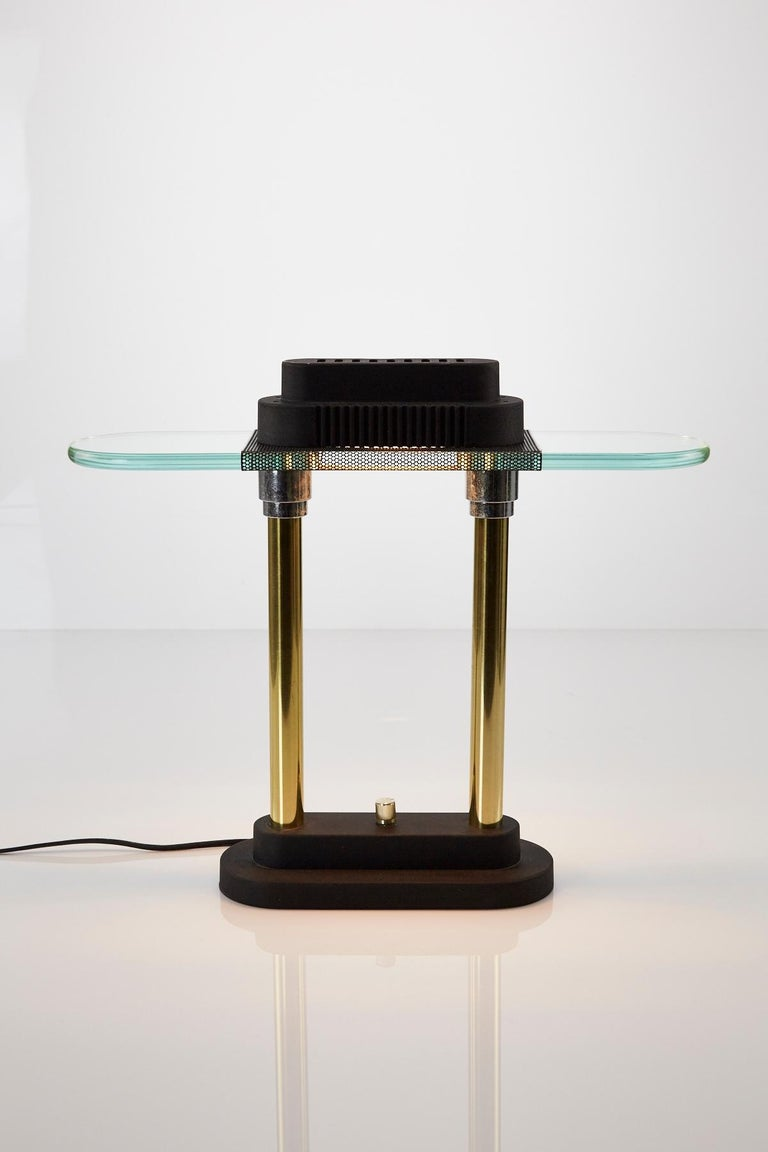 Vintage Postmodern desk or bankers lamp by Robert Sonneman for George Kovacs from the 1980s. This example features brass columns and chrome accents on a matte black base. Oblong glass shade is anchored by black metal mesh and a matte black casing.