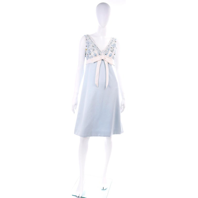 This is a wonderful two piece vintage ensemble that was custom made in Hong Kong in the 1960's.  The outfit has a beaded empire waist dress with a bow and a beaded jacket. We think that this would make the most perfect mother of the bride or mother