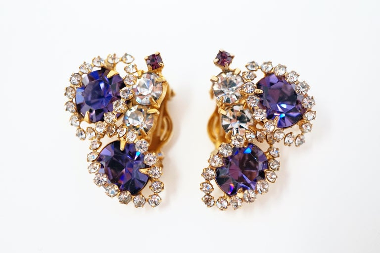 Absolutely gorgeous sparkling rhinestone earrings from the mid-century era, featuring faceted purple crystal rhinestones surrounded by clear crystal rhinestone pavé with gold tone hardware.  DETAILS: - Clip-on earring backs - Each earring measures