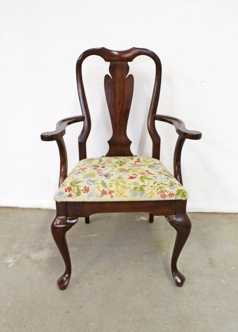 Offered is a vintage Queen Anne arm chair. It's made of solid cherry wood and has a beautifully stitched floral upholstered seat. In good condition for its age, with some slight surface scratches/wear on the wood. The upholstery is in good