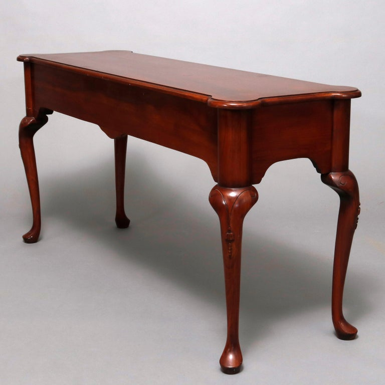A vintage Queen Anne style sofa table by Harden offers mahogany construction with shaped top surmounting deep apron with two drawers and central carved stylized shell and raised on cabriole legs with incised scroll decoration and terminating in pad