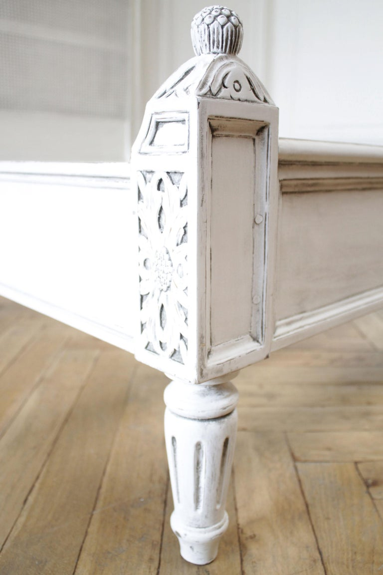 Vintage Queen Louis XVI style platform cane bed Painted in a soft oyster white, with subtle distressed edges, and finished with an antique glazed patina. This does have a cooler tone, as the paint is slightly more a soft silver gray color. Very