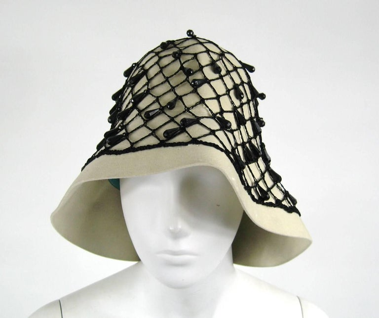 Stunning YSL Vintage Beaded Hat. black Netted beading with a Ribbon Bow at the back. Cream wool fabric. Saks Fifth Ave label as well as YSL label  Finished with a narrow turquoise  grosgrain ribbon. Aside from being decorative it serves to adjust