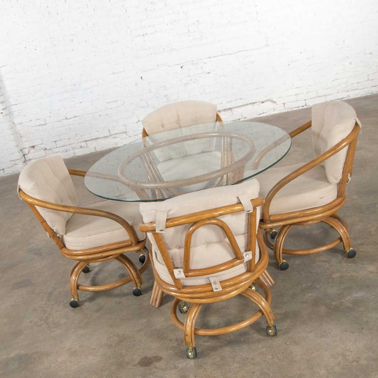 Handsome game table or dining table set including a round glass top rattan base table and four (4) swivel rolling rattan chairs with oatmeal colored upholstered removable seat and back cushions. They are in wonderful vintage condition. The cushions