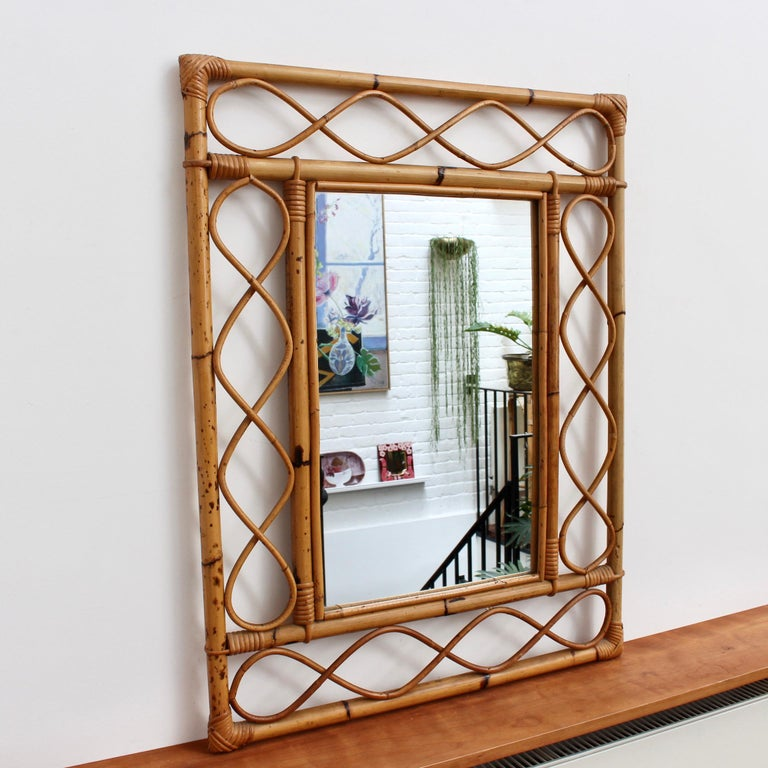 Rectangular French rattan wall mirror (circa 1960s). This is an Asian-inspired design with inner and outer frames connected by figure-eight shapes of rattan cane. The corners are lashed together and protected with rattan strands. Incredibly stylish,