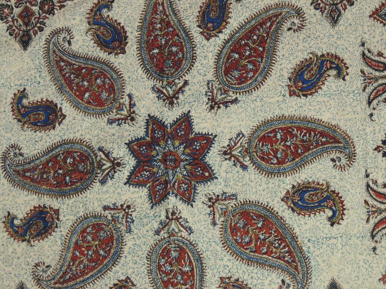 Vintage Red and Blue Paisley Hand-Blocked Cloth with hand-knotted Fringes Kalamkari or qalamkari is a type of hand-painted or block-printed cotton textile, produced in Iran and India. Its name originates in the Persian language which is derived from