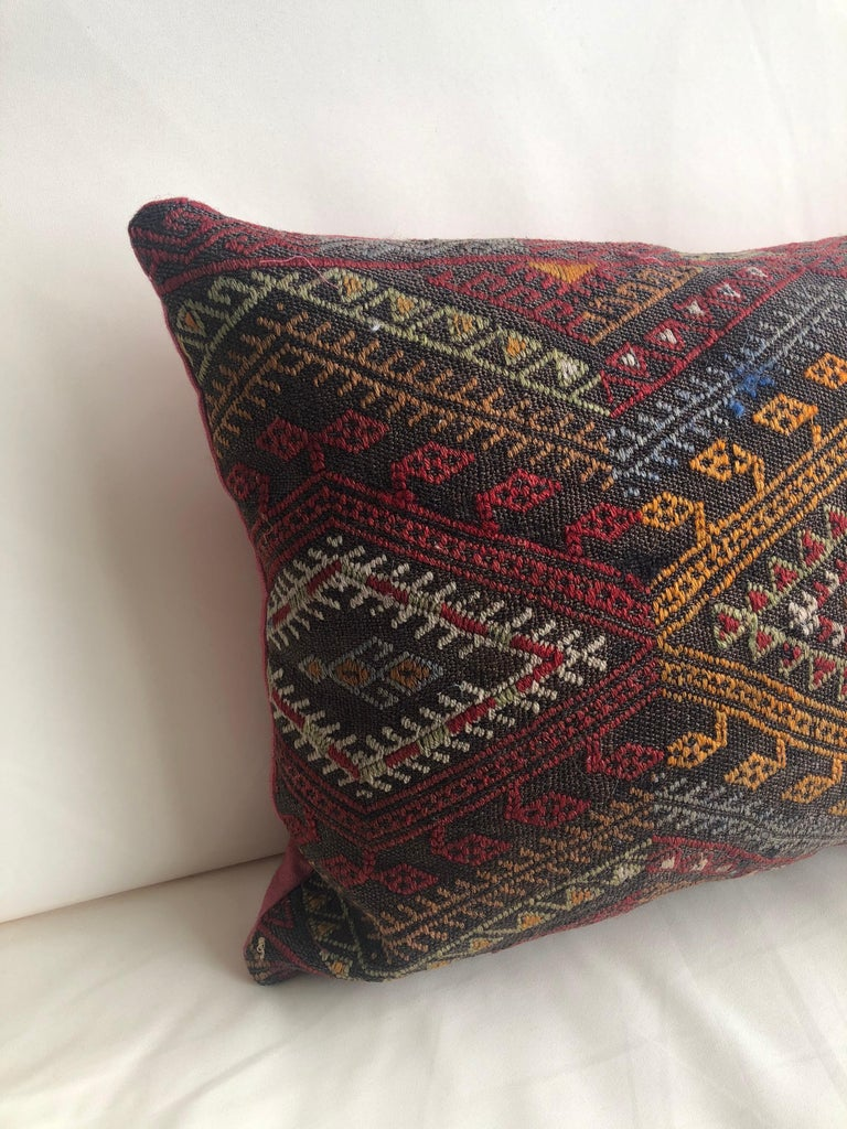 Vintage red and orange woven Kilim bolster decorative pillow with red linen backing. Decorative pillow handcrafted and designed in the USA. Closure by stitch (no zipper closure) with custom made pillow insert.  In shades of red, grey, black,