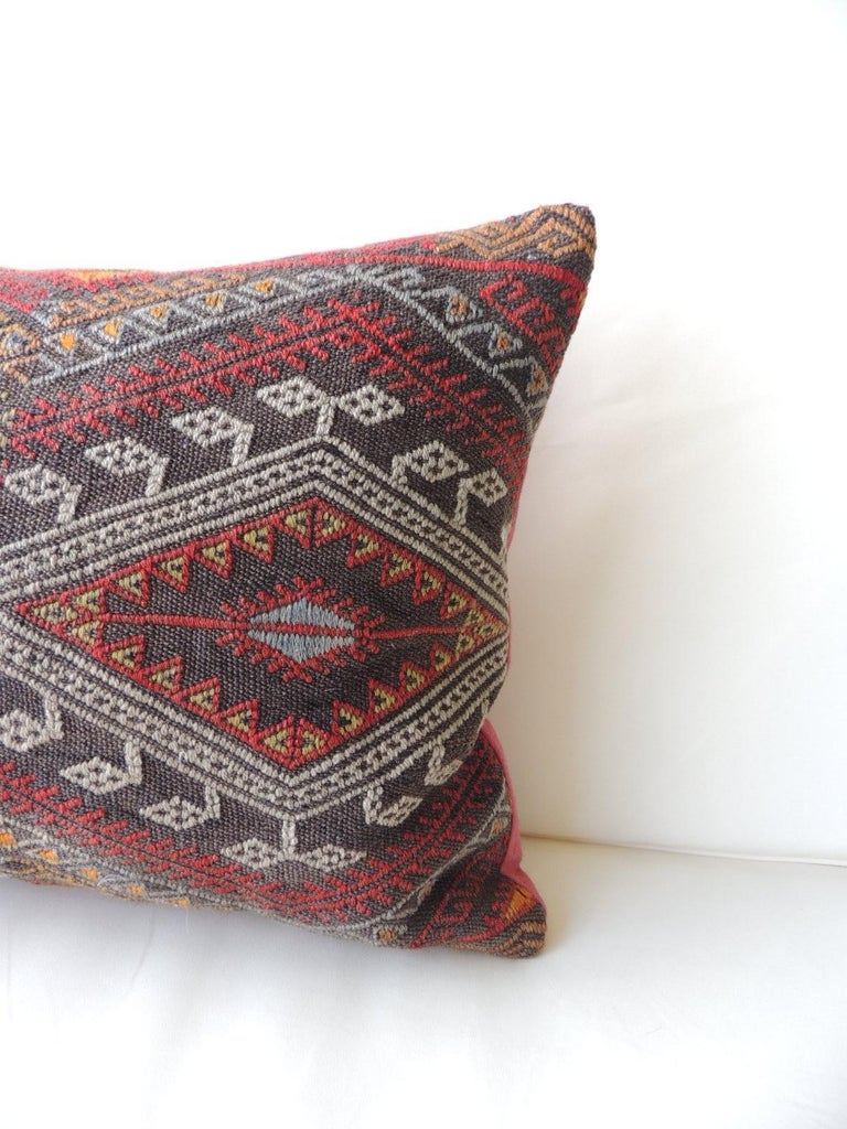 Vintage red and orange woven Kilim bolster decorative pillow with pinkish linen backing. Decorative pillow handcrafted and designed in the USA. Closure by stitch (no zipper closure) with custom made pillow insert. In shades of red, grey, black,