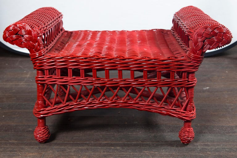 Sturdy, well-made, vintage wicker bench painted red.