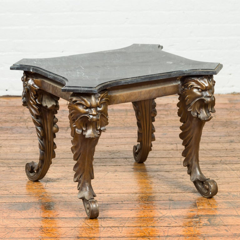 A vintage Renaissance style side table from the mid-20th century with grotesque motifs and black marble top. Created with the traditional technique of the lost-wax (à la cire perdue) that allows a great precision and finesse in the details, this