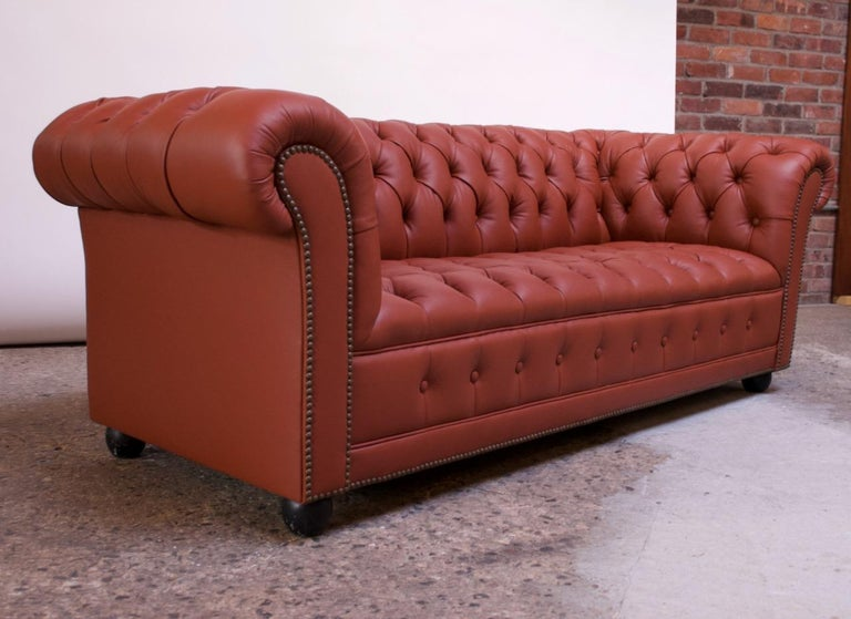 2-seat chesterfield sofa with button tufted detail, newly reupholstered in leather, circa 1970. Exceptional quality; no expense was spared in this full restoration including new foam, double hand-stitching, and applied brass nailhead trim details.