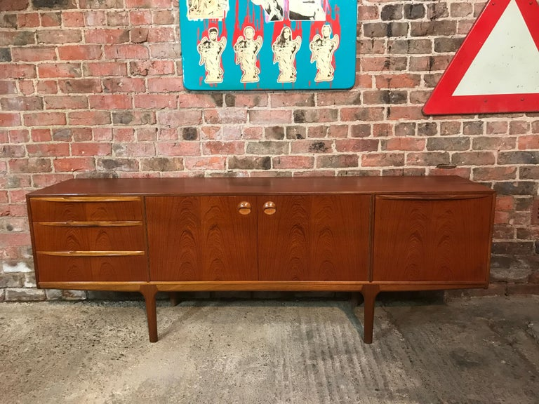 Vintage 1960s McIntosh sideboard by Tom Robertson. It has three drawers, cupboard space with lovely round handles, and a drinks section with a useful pull-out shelf. Credenza is in very good original condition.