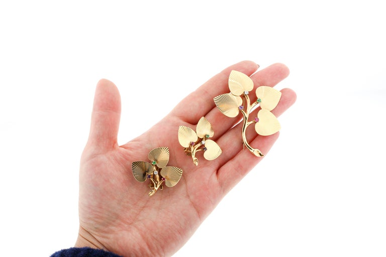 A lovely Retro set of 14k gold leaf earrings with matching pin made by Tiffany & Co. around the 1940s. The textured heart shaped leaves make a cluster set with a small Diamond, Emerald, Amethyst and Emerald. Spelling DEAR. The matching pin has the