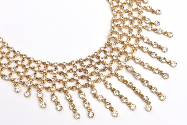 This stunning and elegant cascading bib necklace is filled 4 tiers of rhinestones set in folded metal with hanging stands of the same at the bottom. They are different lengths. You can make it longer or shorter on the neck as there are approx 8