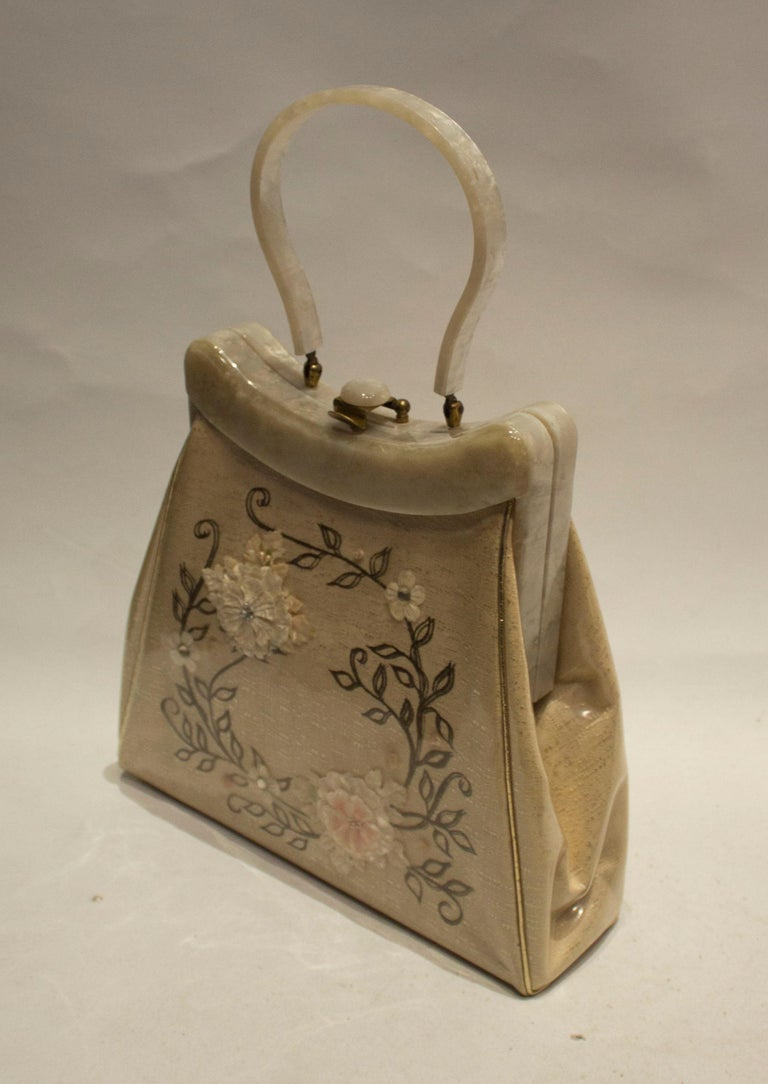 A charming vintage bag from Rialto New York .The bag is embroidered in silk with a plastic overlay. Height 10 1/2'' width 3 1/2''.