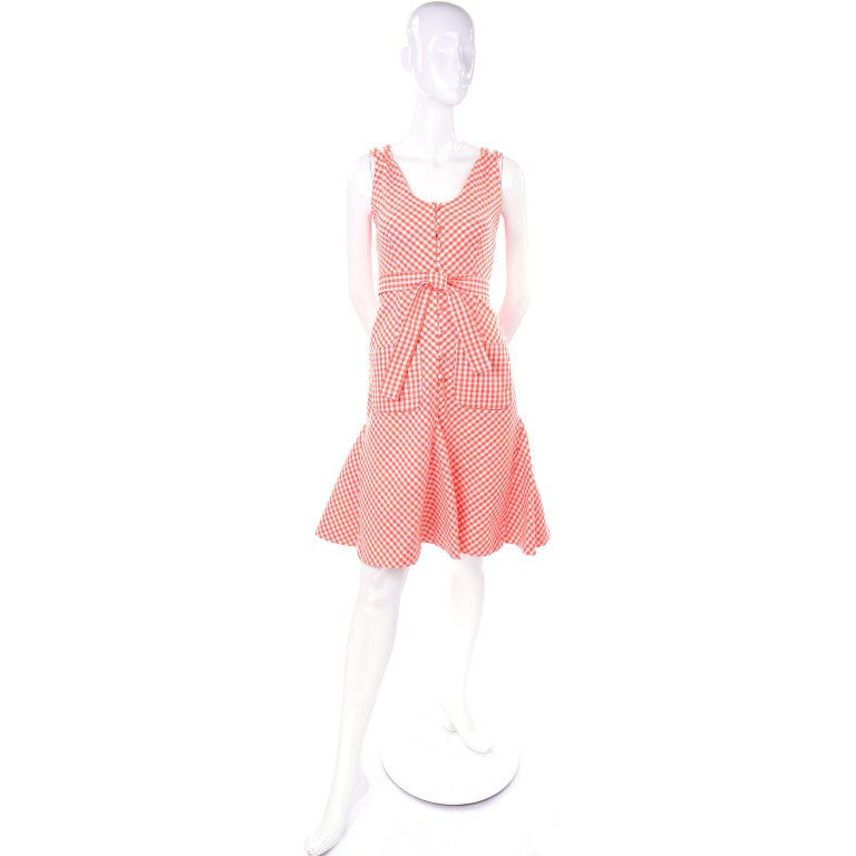 This is such a fun dress designed by Albino Rodrigues. This orange and white gingham  dress has a cross back with double straps and a matching fabric sash or tie that can be worn as a belt or a neck/hair tie. There are two patch pockets at the hips