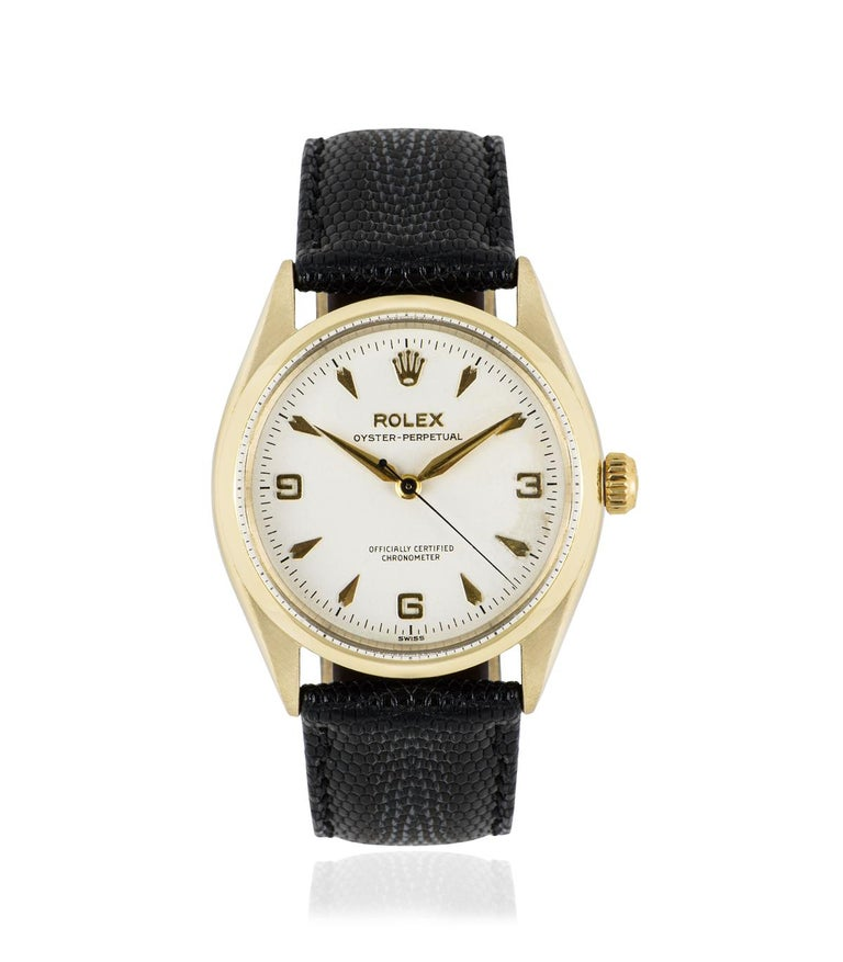 This 34 mm 9k yellow gold vintage Oyster Perpetualby Rolex is in fine condition. Features a silver dial with dagger style hour markers and Arabic numbers 3, 6 and 9. A generic black leather strap comes with a Rolex gold plated pin buckle. Fitted