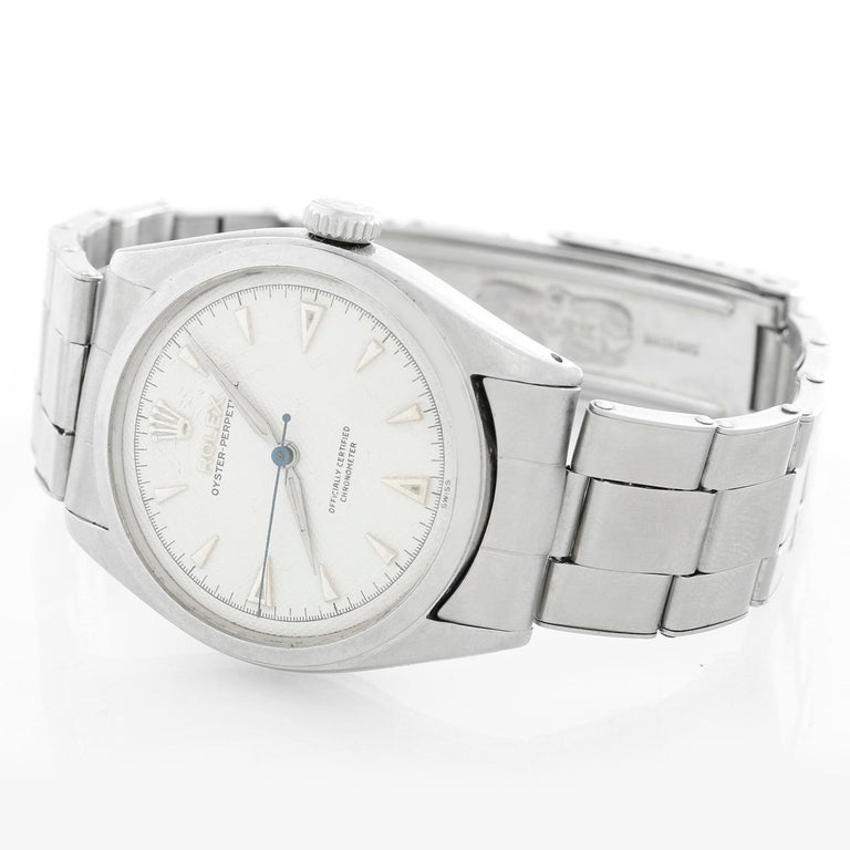Vintage Rolex Oyster Perpetual Stainless Steel Men's Watch Ref. 6084 - Automatic winding. Stainless steel case with smooth bezel ( 34 mm ). White guilloche dial  with luminous hour markers. Stainless Steel Oyster bracelet; will fit up to a 7 1/4